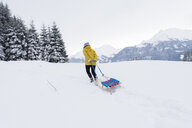Austria, Tyrol, Thurn, back view of woman pulling sledge in snow-covered landscape - PSIF00213