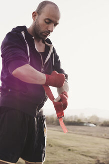 Boxer putting on bandage outdoors - FBAF00240