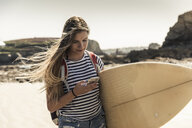 Young woman on the beach, carrying surfboard, using smartphone - UUF16438