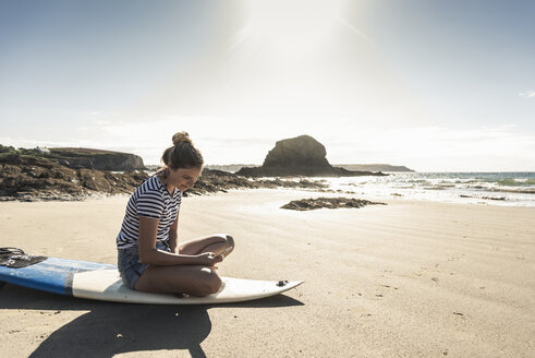 Young woman on the beach, sitting on surfboard, using smartphone - UUF16477