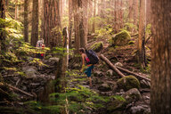 Rock climbers walking through forest, Squamish, Canada - CUF46931