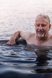 Man in hot tub by lakeside, Johnstone Strait, Telegraph Cove, Canada - CUF46946