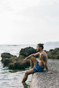 Man sitting on edge of sea - CUF46967