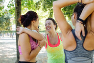 Friends exercising and laughing in park - CUF47003