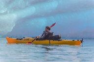 Man kayaking near glacier, Narsaq, Vestgronland, Greenland - CUF47021