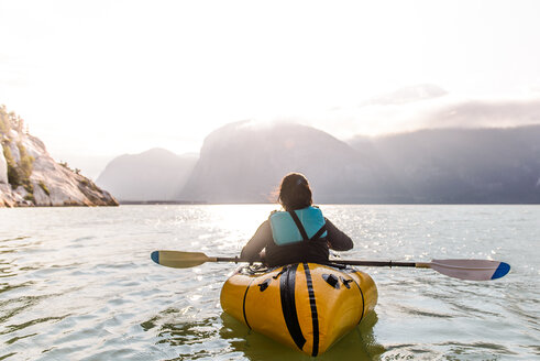 Woman packrafting, Howe Sound bay, Squamish, Canada - CUF47051