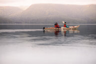 Friends kayaking in lake, Johnstone Strait, Telegraph Cove, Canada - CUF47057