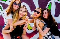 Girlfriends frolicking against graffiti wall - CUF47063
