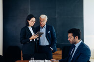 Businessman and woman looking at digital tablet in boardroom - CUF47102