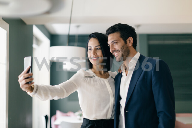 Couple in hotel taking smartphone selfie - CUF47111