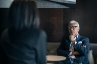 Senior businessman sitting in hotel table meeting with businesswoman, over shoulder view - CUF47114