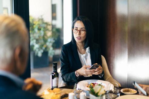 Businesswoman and man having meeting in hotel restaurant - CUF47120