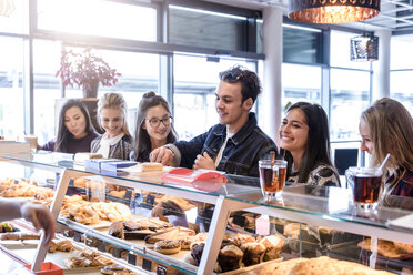 Young male student and female friends queueing at cafe counter - CUF47126