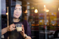 Mid adult woman with coffee looking out from cafe window seat - CUF47129