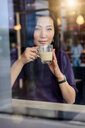 Mid adult woman having coffee in cafe window seat, portrait - CUF47138
