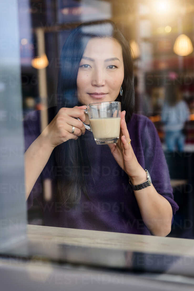 Mid adult woman having coffee in cafe window seat, portrait - CUF47138 - suedhang/Westend61
