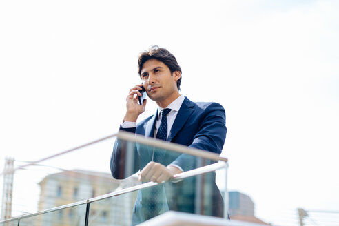 Businessman using smartphone on terrace - CUF47153