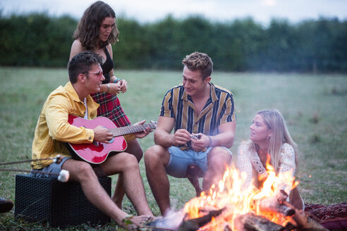 Young man playing guitar at bonfire party in park - CUF47168