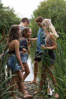 Friends relaxing by lake - CUF47177