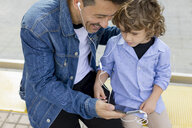 Father and son sitting at tram stop in the city sharing cell phone and earbuds - MAUF02275