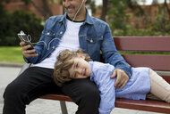 Portrait of smiling boy with father using cell phone and earbuds on a bench - MAUF02278