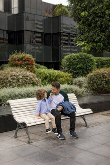 Father and son sitting on a bench in the city - MAUF02287