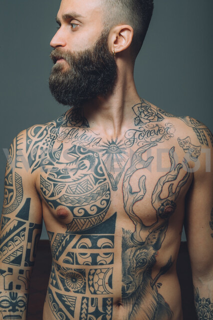 Portrait of  young man with beard, bare chest covered in tattoos - CUF47207