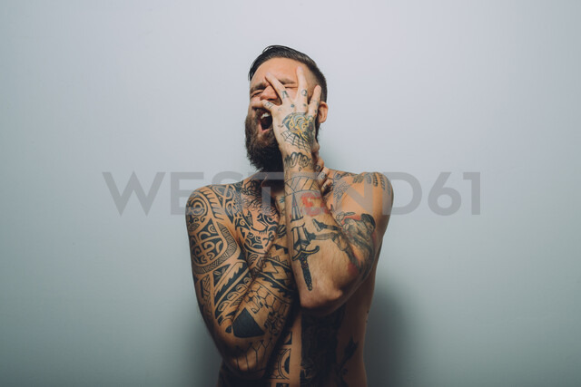 Portrait of young man with beard, covered in tattoos, hand on face, screaming - CUF47210