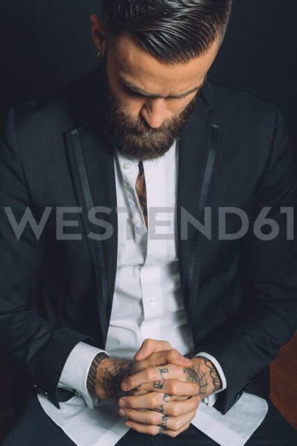 Young man wearing suit, sitting with hands clasped, tattoos on hands, pensive expression - CUF47216