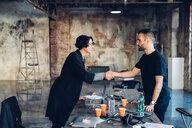 Business people shaking hands in studio - CUF47219