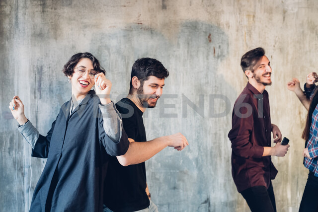 Friends dancing against backdrop of concrete wall - CUF47222