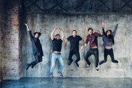 Colleagues in jumping pose for group photo against concrete wall - CUF47225