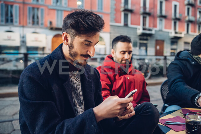 Man using smartphone at outdoor cafe, Milan, Italy - CUF47240
