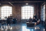 Designers brainstorming in communal space in studio - CUF47243