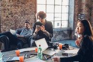 Designers brainstorming in communal space in studio - CUF47249
