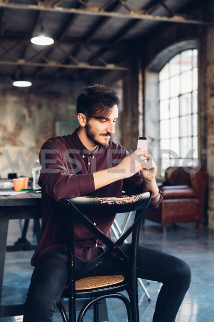 Man sitting back to front on chair using smartphone - CUF47261