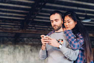 Woman looking over shoulder of man using smartphone - CUF47282