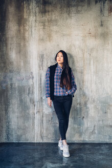 Woman leaning against concrete wall - CUF47291