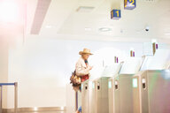 Young woman at airport, walking through turnstile - CUF47300