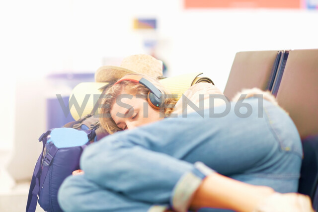 Young woman at airport, sleeping on seating in departure lounge - CUF47303