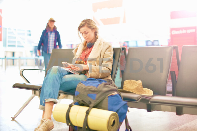 Young woman at airport, sitting with backpack beside her, using smartphone - CUF47306