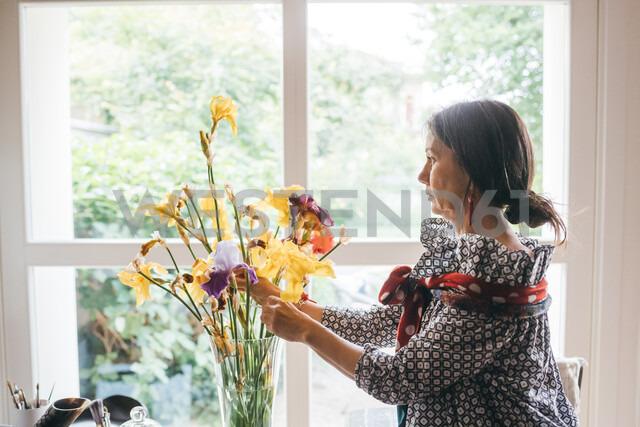 Woman arranging flowers in vase - CUF47309