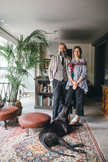 Couple with their dog in living room at home - CUF47312