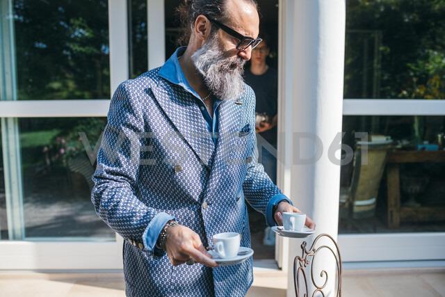 Man having coffee on patio - CUF47342