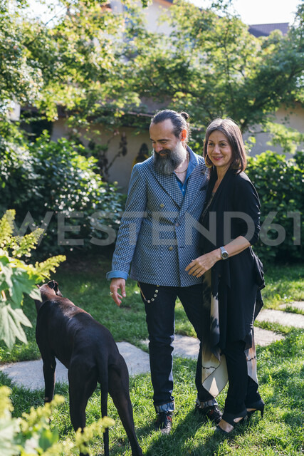 Couple with pet dog in garden - CUF47345