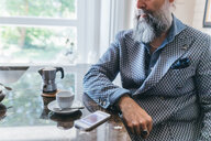 Man using cellphone over coffee in kitchen - CUF47348