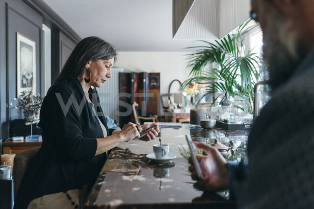Couple using cellphone over coffee in kitchen - CUF47351