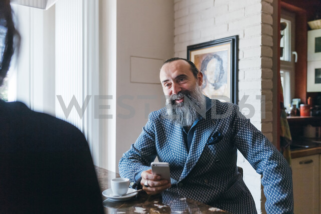 Man using cellphone and talking to friend in kitchen - CUF47357