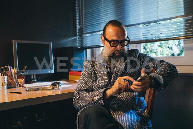 Man using cellphone at desk - CUF47369