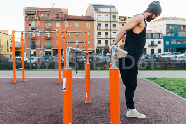Man using parallel bars in outdoor gym - CUF47381